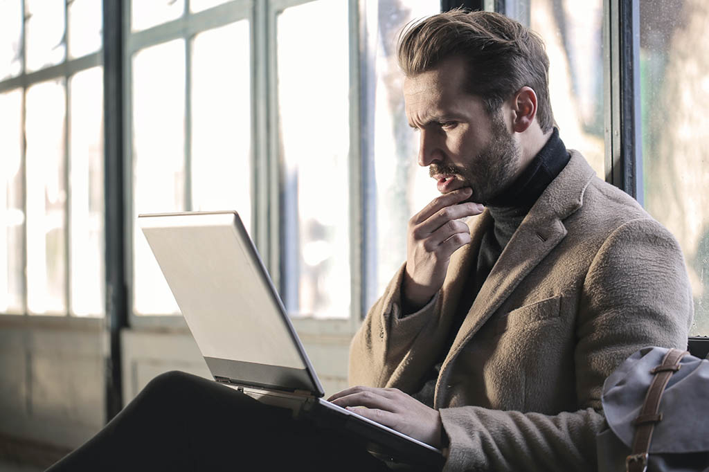concerned looking man looking at laptop