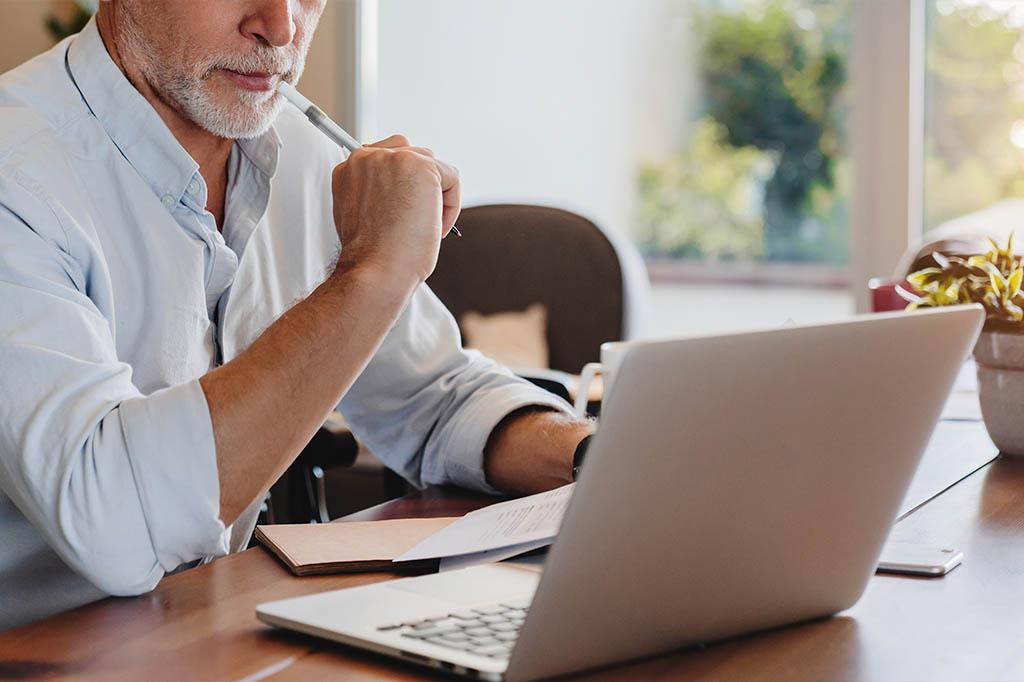 man reviewing treatment plan on laptop