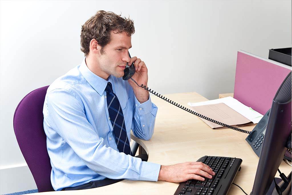 man talking on phone while typing on computer