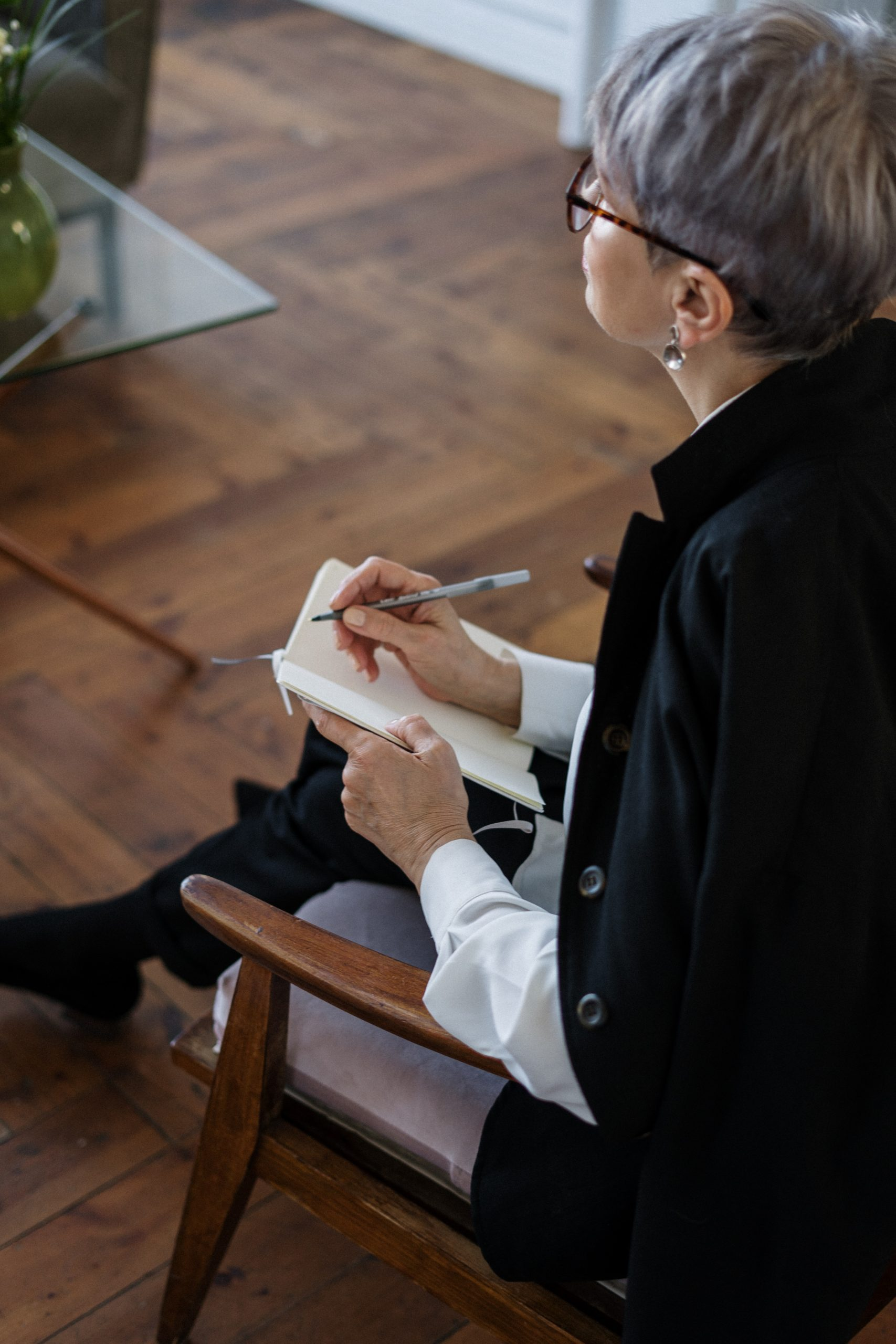 woman sitting and writing in notebook